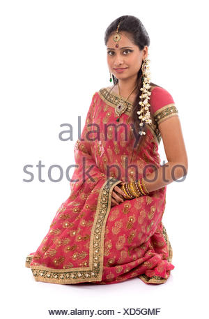 Portrait of full body traditional Indian girl in sari clothes smiling, kneeling on floor isolated on white background. - Stock Photo
