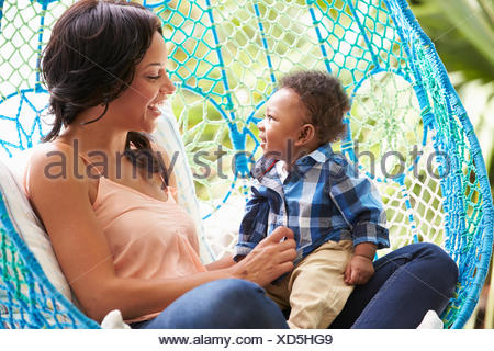Mother With Baby Son Relaxing On Outdoor Garden Swing Seat - Stock Photo
