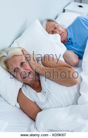 Senior woman covering ears while man snoring - Stock Photo
