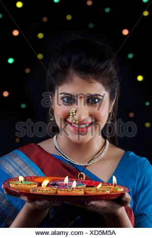 Maharashtrian woman holding a tray of diyas - Stock Photo