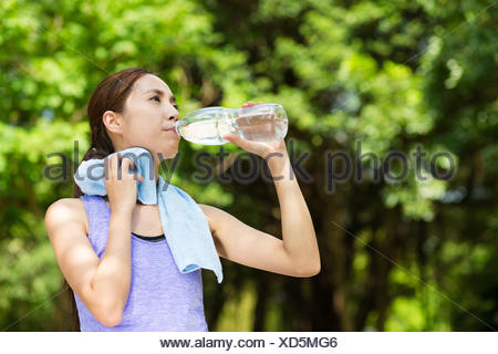 Beautiful young asian woman drinking water after training - Stock Photo