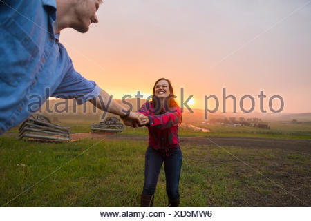 Woman pulling man in rural field at sunset - Stock Photo