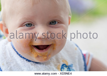Close up of baby with dirty face after eating - Stock Photo