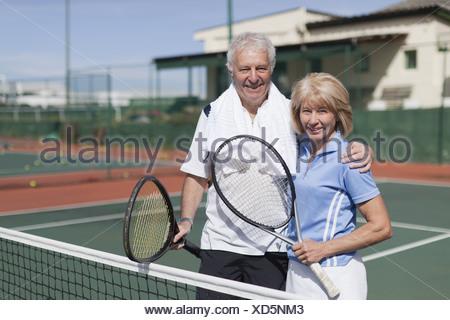 Older couple hugging on tennis court - Stock Photo