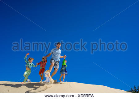 Father and three children running down a sand dune - Stock Photo