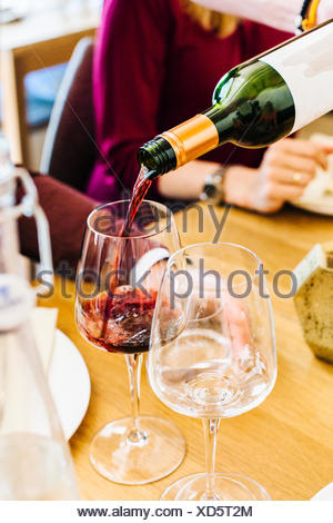Red wine being poured in glass at restaurant table - Stock Photo