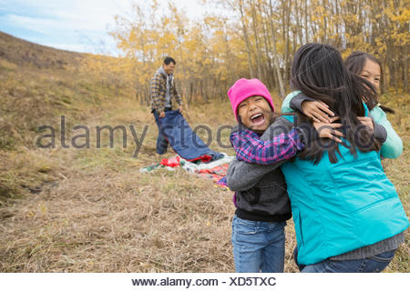 Mother and daughters hugging in field - Stock Photo