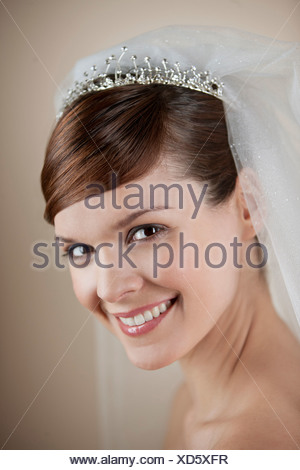 A young bride wearing a tiara and veil, smiling - Stock Photo