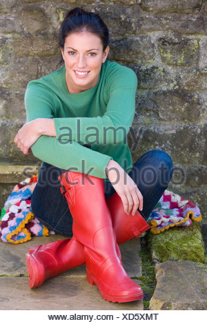 Smiling woman in rubber boots leaning against wall - Stock Photo