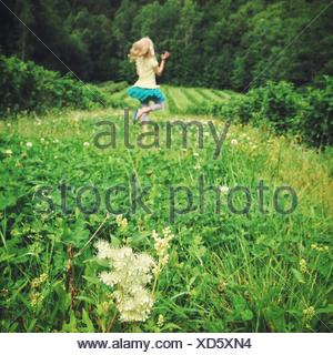 Girl (12-13) jumping on meadow - Stock Photo