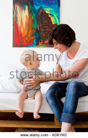 Mother and baby sitting on couch - Stock Photo