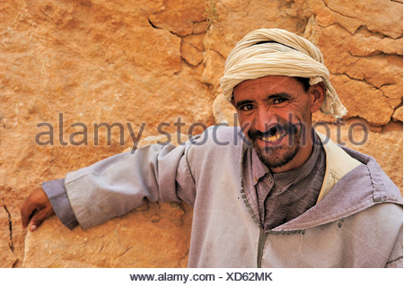 Portrait of a friendly man wearing a traditional djellaba and turban leaning against a rock wall, Todra Gorge, Morocco, Africa - Stock Photo