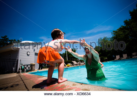 A small girl reaches for mom in the pool. - Stock Photo