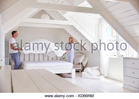 Couple Wearing Pajamas Making Bed In Morning - Stock Photo