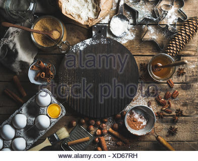 Christmas holiday cooking and baking ingredients. Cookie molds, spices, flour, eggs, cocoa powder, sugar, honey, nuts on rustic - Stock Photo