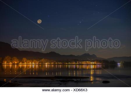 Vollmond ueber dem Chiemsee, Beleuchtung von Strasse und Gebaeuden spiegelt sich im See , Deutschland, Bayern, Chiemsee | illumi - Stock Photo