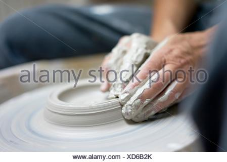 hands of passionate potter creating a fine piece of craftmanship. - Stock Photo