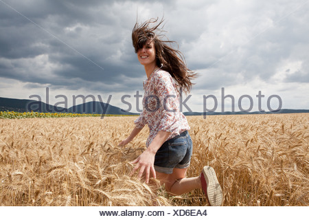Mid adult woman running through wheat field - Stock Photo