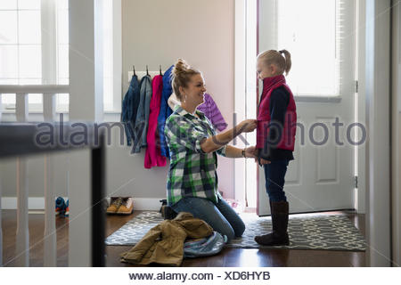 Mother zipping vest on daughter at front door - Stock Photo