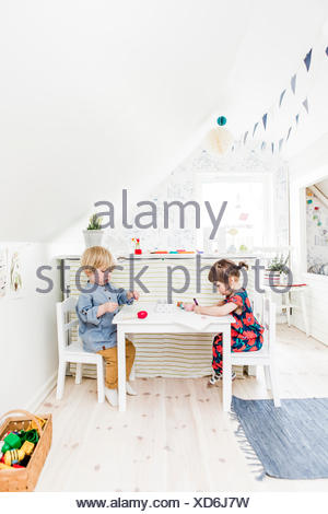 Sweden, Boy and girl (2-3) playing in bedroom - Stock Photo