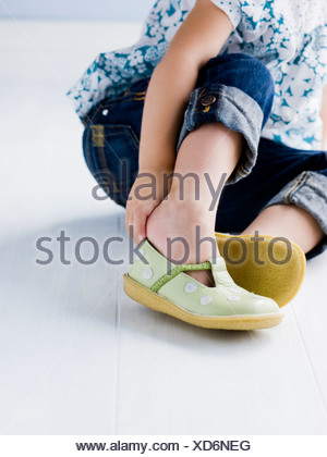 little girl putting on her shoes - Stock Photo