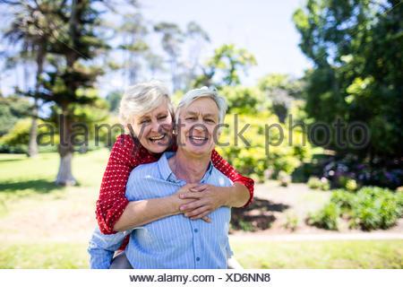 Happy senior man giving a piggy back to senior woman - Stock Photo