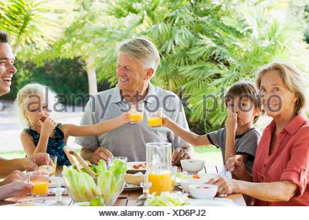 Multi-generation family enjoying meal outdoors - Stock Photo