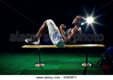 Portrait of american football player doing sit ups - Stock Photo