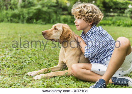 Portrait of boy sitting petting dog in garden - Stock Photo