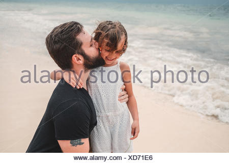 Father kissing daughter on beach, Cancun, Mexico - Stock Photo