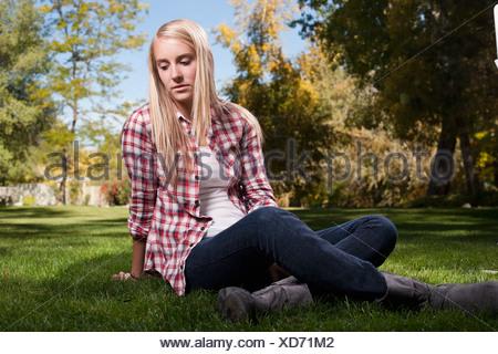 USA, Utah, outdoor portrait of blonde teenage girl (14-15) sitting on grass - Stock Photo