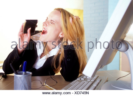 Female straight long blonde hair wearing dark suit white shirt sitting at desk hands in hair drinking from hip flask glasses - Stock Photo