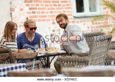 Sweden, Skane, Three people at cafe eating lunch - Stock Photo