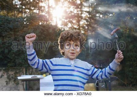 Boy arms raised holding sausage on fork smiling - Stock Photo