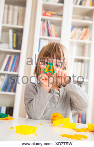 Little girl cutting out yellow modeling clay - Stock Photo