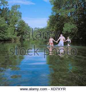 Man and two girls wading in river - Stock Photo