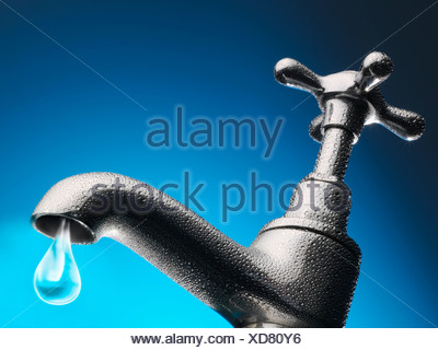 Drop of water trickling from tap, close-up (digital composite) - Stock Photo