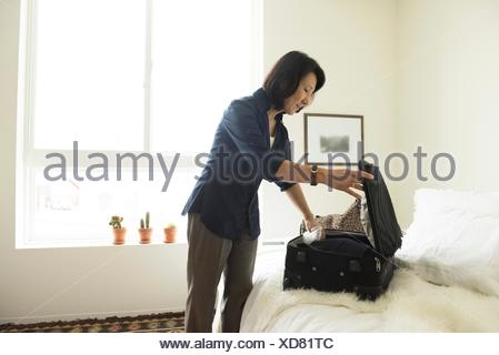 Mature woman standing in hotel room packing suitcase - Stock Photo