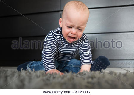 Crying baby boy sitting on rug in living room - Stock Photo
