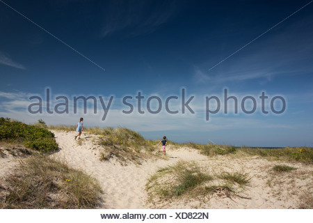 Brother and sister running over sand dunes - Stock Photo