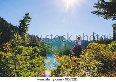 Young boy (2-3) sitting on father's shoulders looking at mountain - Stock Photo