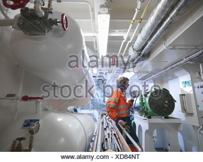 Engineer in ship's engine room - Stock Photo