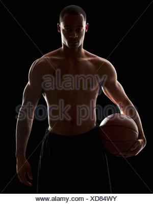 Studio portrait of shirtless man holding basketball - Stock Photo