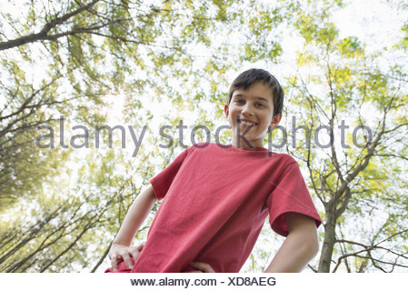 A young boy in  woodland looking around curiously. - Stock Photo
