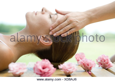 Woman lying on deck, surrounded with flowers, having head massage - Stock Photo