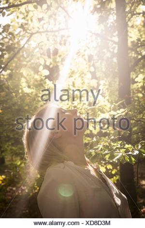 Mature woman standing in stream of light in forest - Stock Photo