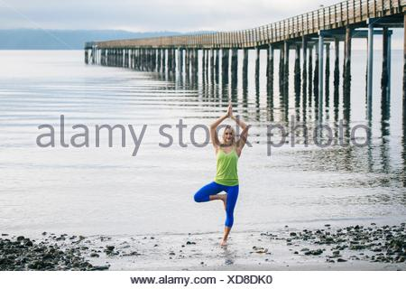 Portrait of young woman practicing yoga standing tree pose on beach - Stock Photo