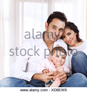 Happy family at home, sweet little daughter having fun with mother and father, happy parenthood, togetherness concept - Stock Photo