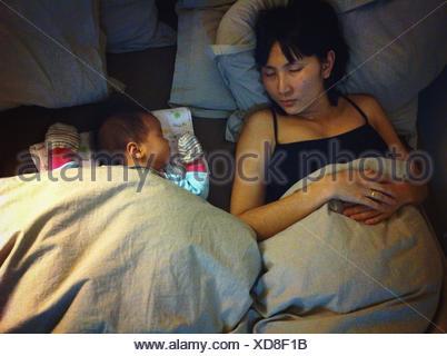 Baby Girl Sleeping With Mother - Stock Photo