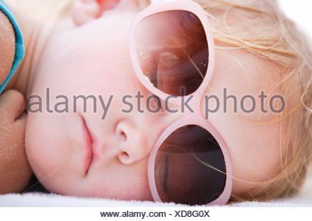 little girl sleeping on the beach, portrait - Stock Photo